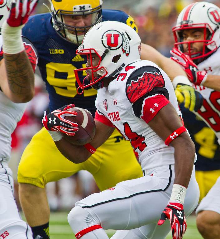 . Utah running back Bubba Poole (34) rushes with the ball in the first quarter of an NCAA college football game against Michigan in Ann Arbor, Mich., Saturday, Sept. 20, 2014. (AP Photo/Tony Ding)
