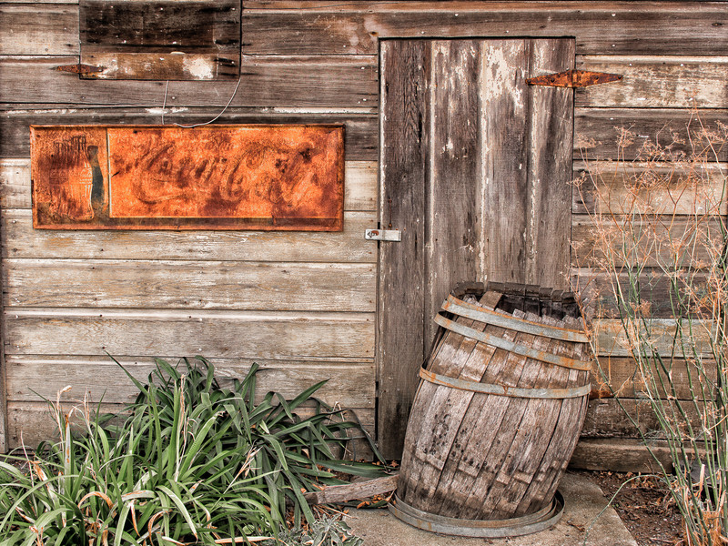 Old Door, Rusted Coca-Cola Sign and Delapidated Wooden Barrel