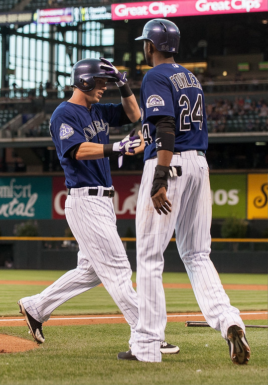 . Corey Dickerson #6 and Dexter Fowler #24 of the Colorado Rockies celebrate a pair of first inning runs against the San Diego Padres during a game at Coors Field on August 12, 2013 in Denver, Colorado. The Rockies led the Padres 2-0 after one inning.  (Photo by Dustin Bradford/Getty Images)