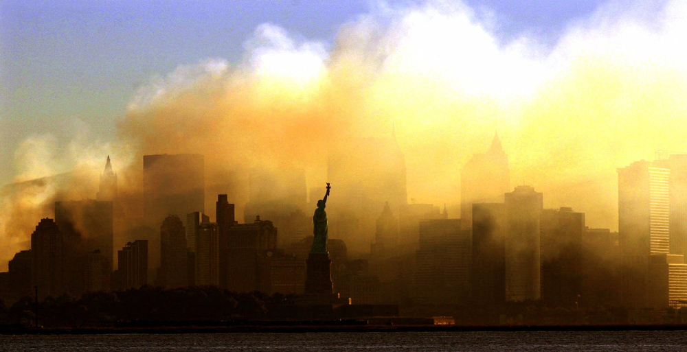 . The Statue of Liberty can be seen at first light from a view from Jersey City, N.J., as the lower Manhattan skyline is seen though a thick smoke filled the sky early Saturday, Sept. 15, 2001.  (AP Photo/Dan Loh)