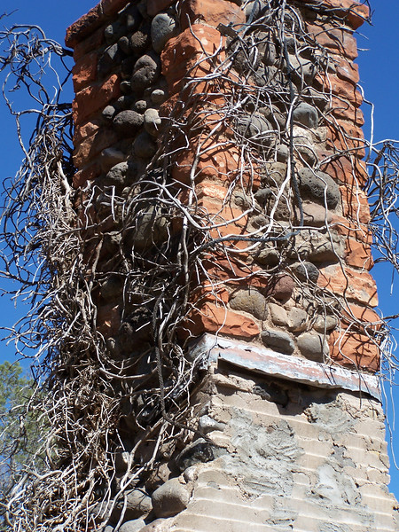 The chimney from a former ranch building marks the beginning of the 1/3 mile trail to the red sandstone wall containing the petroglyphs.
