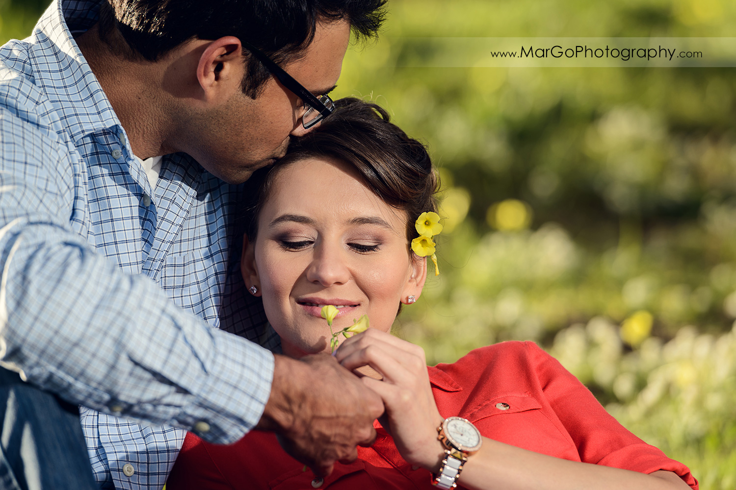 close-up of man in blue shirt giving yellow flower to woman in red dress during engagement session at San Francisco Legion of Honor