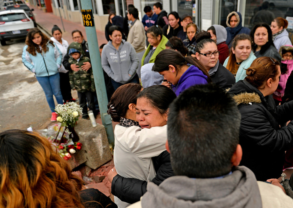 . Blanca Palomino gets a hug from a family friend at the corner of East Colfax Avenue and Dayton Street in Aurora where her older son, Juan Carlos Dominguez-Palomino, was killed earlier in a fatal crash, Monday, March 24, 2014. (Photo by RJ Sangosti/The Denver Post)