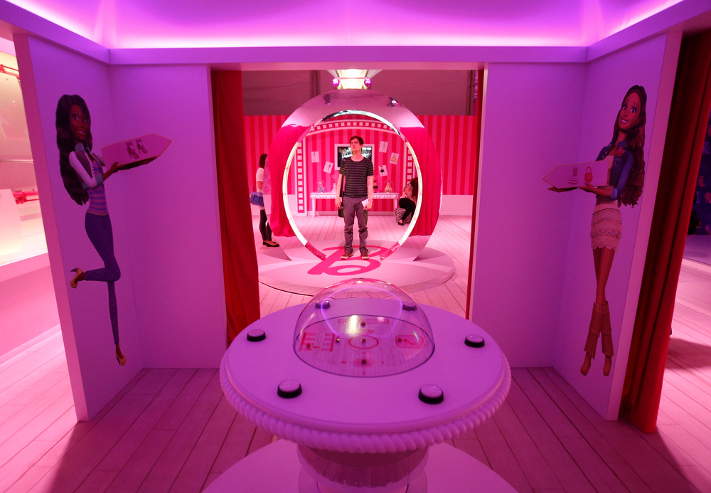 """. A visitor stands inside a \""""Barbie Dreamhouse\"""" of Mattel\'s Barbie dolls in Berlin, May 16, 2013. The life-sized house, covering about 1,400 square metres offers visitors to try on Barbie\'s clothes in her walk-in closet, tour her living room and her kitchen.   REUTERS/Fabrizio Bensch"""