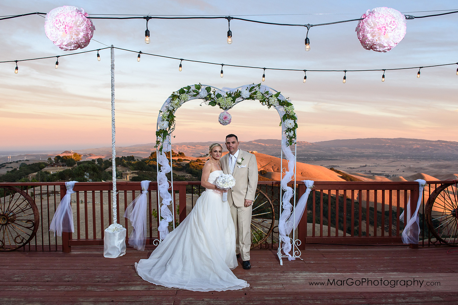 portrait of the bride and groom on the backyard deck with sunset hills view