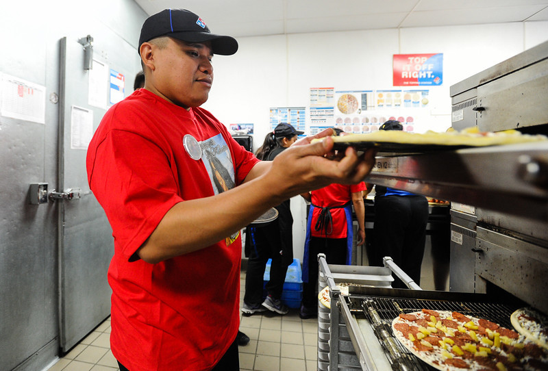 . Felipe Kantun, brother of slain Domino\'s Pizza manager Nelly Kantun, helps make pizzas during an-all-day memorial fundraiser for her aunt at Domino\'s Pizza on Highland Avenue in San Bernardino, CA on Wednesday, Feb. 19, 2014. Kantun, who worked as a Domino\'s employee for more than 20 years, was gunned down at the pizza location on Feb. 12. (Photo by Rachel Luna / San Bernardino Sun)