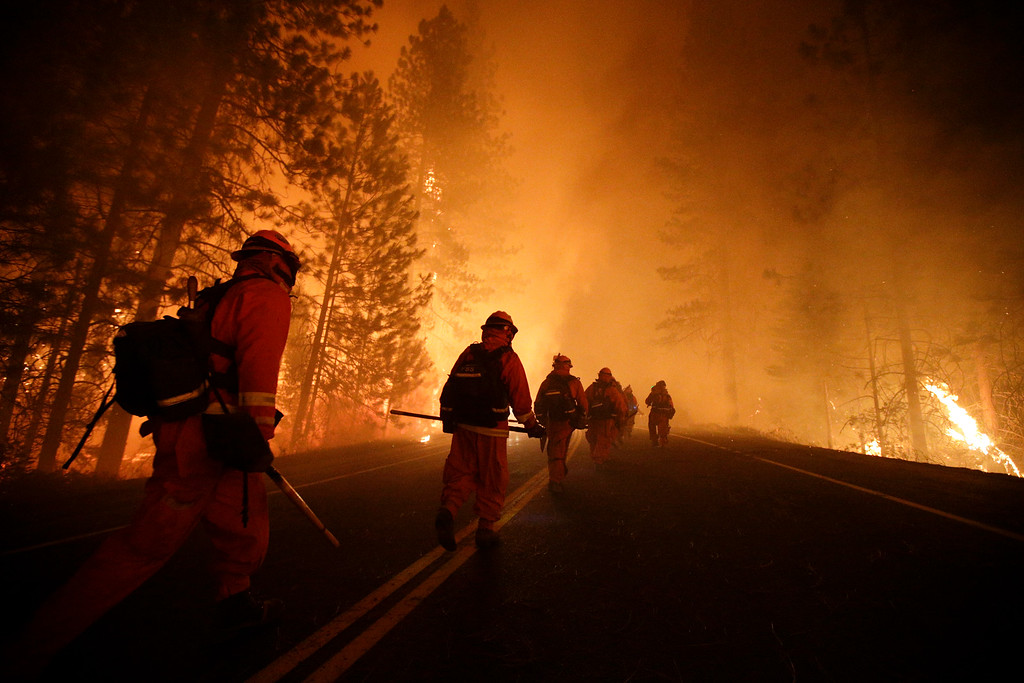. Inmate firefighters walk along state Highway 120 as firefighters continue to battle the Rim Fire near Yosemite National Park, Calif., on Sunday, Aug. 25, 2013.  (AP Photo/Jae C. Hong)