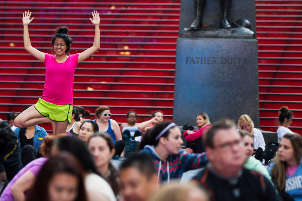 """. A woman poses for her friend as they take part in a group yoga practice on the morning of the summer solstice in New York\'s Times Square, June 21, 2013. The \""""Solstice in Times Square\"""" event on Friday brought out thousands of participants to celebrate the year\'s longest day in New York. REUTERS/Lucas Jackson"""