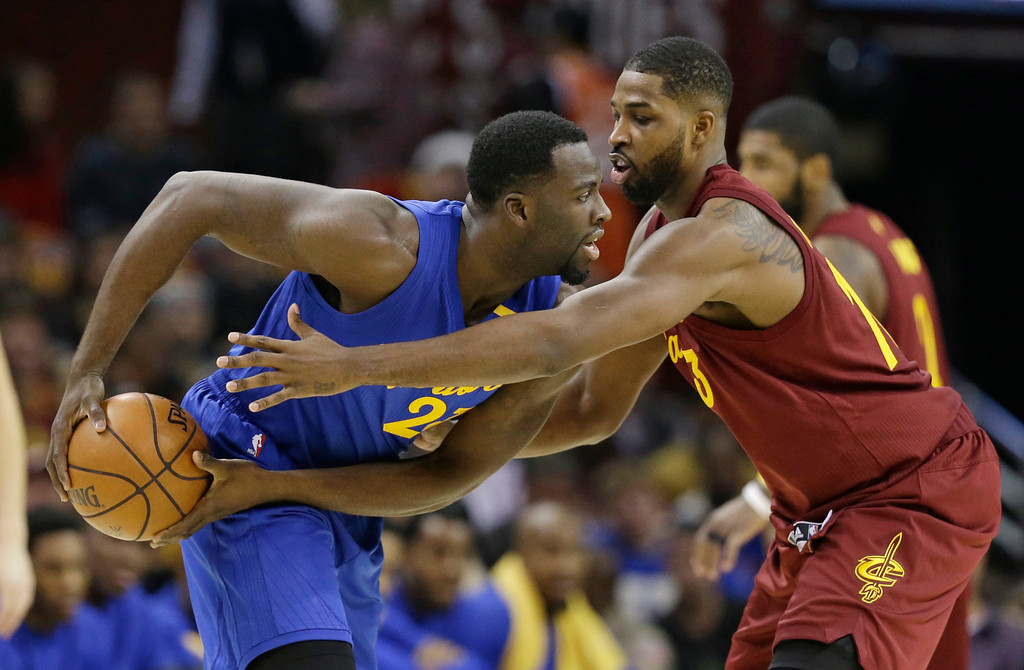 . Cleveland Cavaliers\' Tristan Thompson, right, puts pressure on Golden State Warriors\' Draymond Green in the first half of an NBA basketball game, Sunday, Dec. 25, 2016, in Cleveland. (AP Photo/Tony Dejak)
