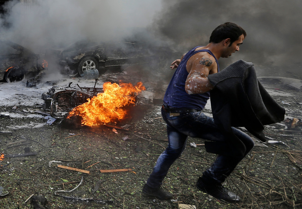 . A Lebanese man runs in front of a burned car, at the scene where two explosions have struck near the Iranian Embassy killing many, in Beirut, Lebanon, Tuesday Nov. 19, 2013.  (AP Photo/Hussein Malla)