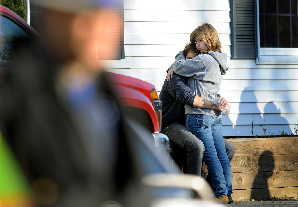 . People embrace at a firehouse staging area for family around near the scene of a shooting at the Sandy Hook Elementary School in Newtown, Conn. where authorities say a gunman opened fire, leaving 27 people dead, including 20 children, Friday, Dec. 14, 2012. (AP Photo/Jessica Hill)
