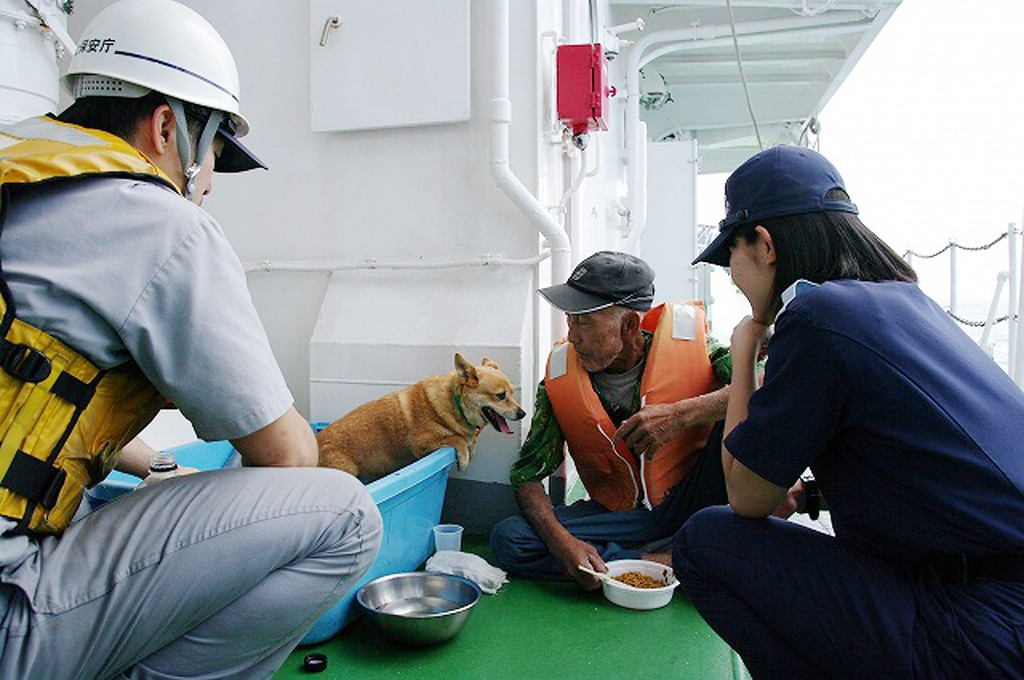 . This handout picture taken and released by the Japan Coast Guard on May 29, 2015 shows an elderly man (2nd R) and his dog being evacuated onboard a coast guard vessel from Kuchinoerabu island after the island\'s volcano erupted in Kagoshima prefecture of Japan\'s southern island of Kyushu. A violent volcanic eruption in southern Japan forced the evacuation of an island, as a huge column of ash was shot high into the sky. AFP PHOTO / JAPAN COAST GUARD/AFP/Getty Images
