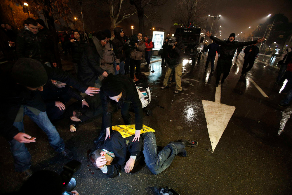 . Protesters lie on the ground after clashes with riot police during a protest against high electricity prices in Sofia February 19, 2013. Bulgaria\'s Prime Minister Boiko Borisov sought to calm mass protests on Tuesday by promising to slash electricity prices and punish foreign-owned power companies, setting Bulgaria on a collision course with EU partner the Czech Republic. REUTERS/Stoyan Nenov