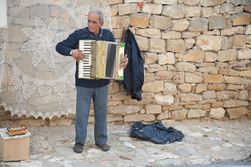 Street musician standing in front of Bulgarian lace for sale. Arbanasi, Bulgaria.