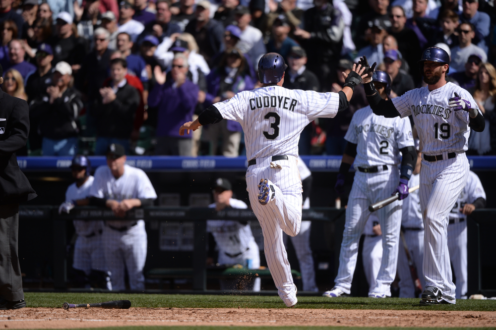 . Michael Cuddyer high fives Charlie Blackmon after scoring a run on a triple by Carlos Gonzalez during the third inning. The Colorado Rockies hosted the Arizona Diamondbacks in the Rockies season home opener at Coors Field in Denver, Colorado Friday, April 4, 2014. (Photo by Karl Gehring/The Denver Post)