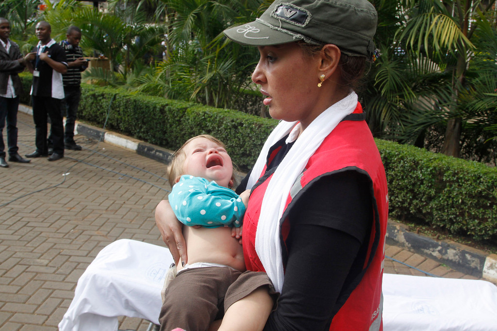 . A Red Cross assistant helps a child outside the Westgate Mall in Nairobi, Kenya Saturday, Sept. 21, 2013, after gunmen threw grenades and opened fire during an attack that left multiple dead and dozens wounded. A witness to the attacks on the upscale shopping mall says that gunmen told Muslims to stand up and leave and that non-Muslims would be targeted. (AP Photo/Khalil Senosi)