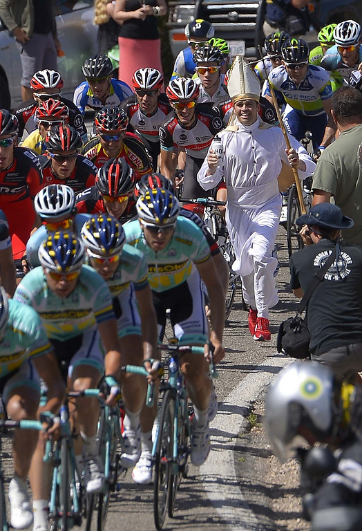 . A spectator dressed as a pope runs with the peloton during the fourth stage of the Tour of California cycling race, Wednesday, May 15, 2013, in Ojai, Calif.  (AP Photo/Mark J. Terrill)