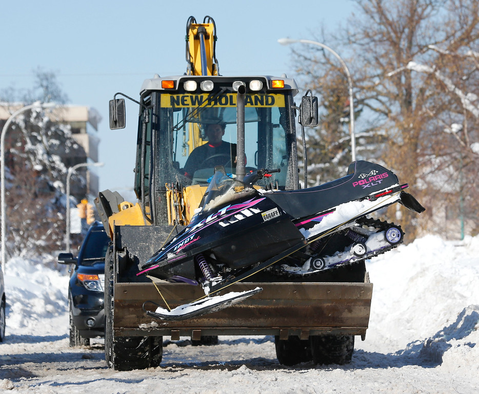 . A backhoe carries a broken down snowmobile in the south Buffalo area on Friday, Nov. 21, 2014, in Buffalo, N.Y. A snowfall that brought huge drifts and closed roads in the Buffalo area finally ended Friday, yet residents still couldn\'t breathe easy, as the looming threat of rain and higher temperatures through the weekend and beyond raised the possibility of floods and more roofs collapsing under the heavy loads. (AP Photo/Mike Groll)