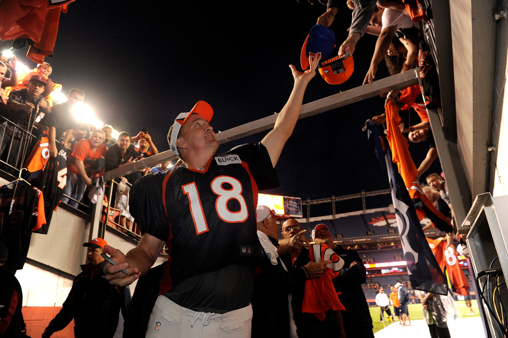. DENVER, CO. - AUGUST 03: Quarterback Peyton Manning reached for a hat to sign Saturday night. The Denver Broncos signed autographs for fans after practicing in the rain at Sports Authority Field Saturday night, August 3, 2013. Photo By Karl Gehring/The Denver Post