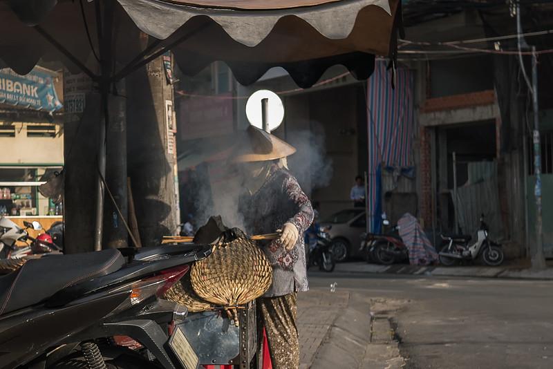 A vendor prepares food on a street corner.