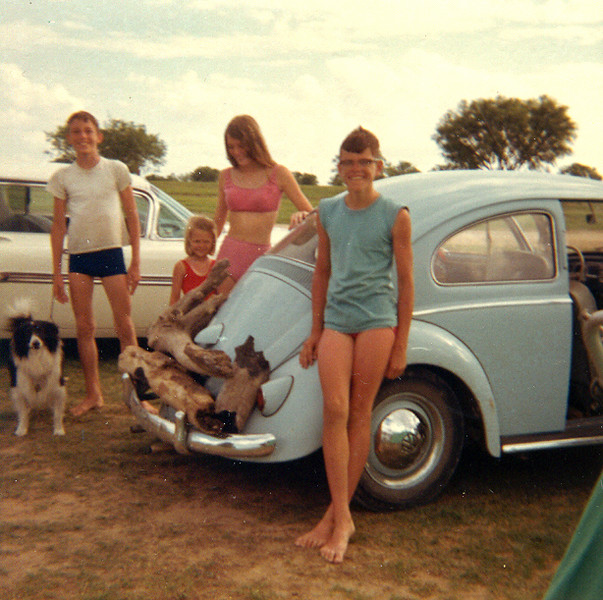 "THE DUNCAN COUSINS God, what a scrawny bunch we were back then! Here we are, seen here with the two family cars of ours, the white 1959 Chevrolet Impala and Dad's ""new"" blue 1958 VW Beetle (note the Euro turn signals on the door post). I learned to drive in that car, just ask my sister, Lyn. What a wild ride I gave her that first time I got behind the wheel. She didn't know I'd never actually driven before.   L to R: Bolivar (Uncle Linuel's border collie), Carl, Stacey, Carol, and me."