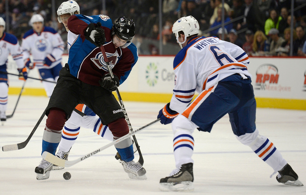 . Matt Duchene (9) of the Colorado Avalanche tries to gain control of the puck as Ryan Whitney (6) of the Edmonton Oilers comes in on defense during the first period March 12, 2013 at Pepsi Center. (Photo By John Leyba/The Denver Post)