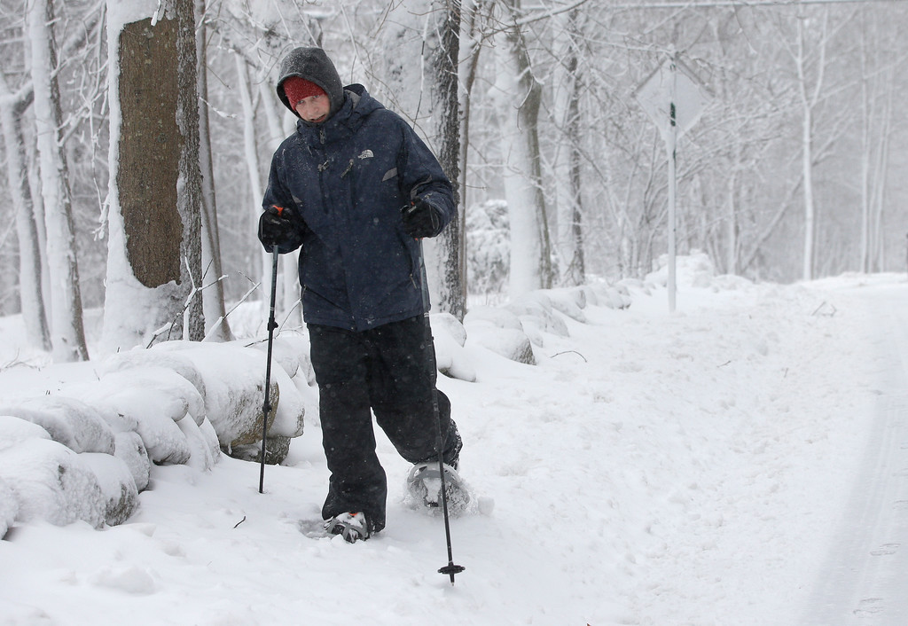 . Joe Donaghey, of Norwell, Mass., snowshoes along a road during a storm in Norwell, Tuesday, March 13, 2018. The nor\'easter is expected to deliver up to 2 feet of snow to some areas of New England. (AP Photo/Steven Senne)