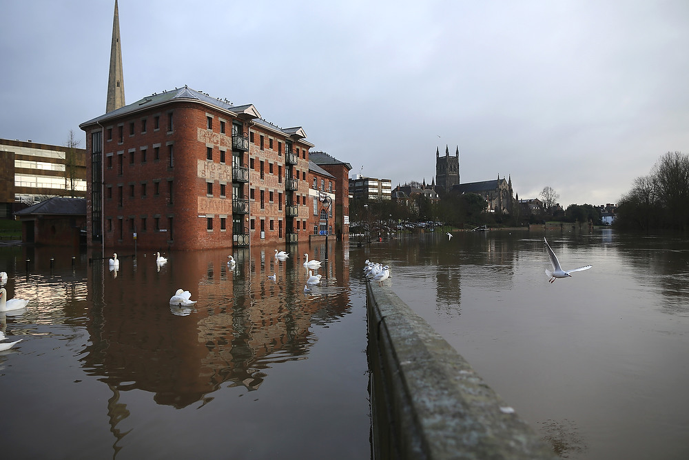 . The River Severn breaks it\'s banks in the city of Worcester after heavy rainfall on December 24, 2012 in Worcester, England. Forecasters have predicted more rain to sweep across the country causing flash flooding over the coming days.  The Southwest of England has been badly affected causing major disruption to the rail network delaying journeys for people making their way home for Christmas.  (Photo by Christopher Furlong/Getty Images)