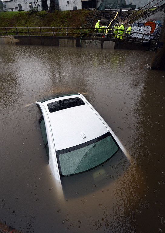 . The roof of a car protrudes above the floodwaters at the Ashby Avenue railroad underpass in Berkeley, Calif., on Thursday, Dec. 11, 2014. (Kristopher Skinner/Bay Area News Group)