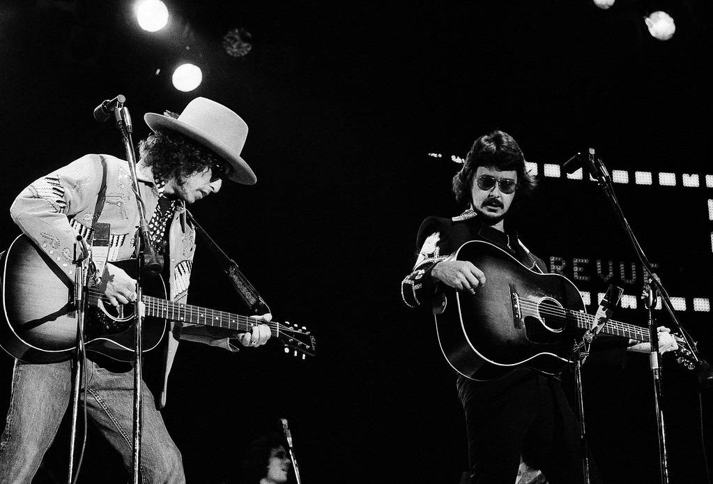 ". Musician Bob Dylan and the Rolling Thunder Revue perform at a benefit concert for boxer Rubin ""Hurricane"" Carter, January 1976. Musician Bob Neuwirth is at right. (AP Photo)"