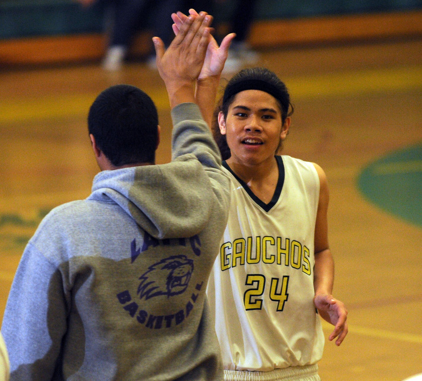. Narbonne\'s Shailo Leafa (24) is high-fived during a time out as time dwindles with San Pedro trailing in a Marine League basketball game Friday evening. Narbonne won the game 47-41 in front of their home crowd. February 12, 2010.  Photo by Steve McCrank