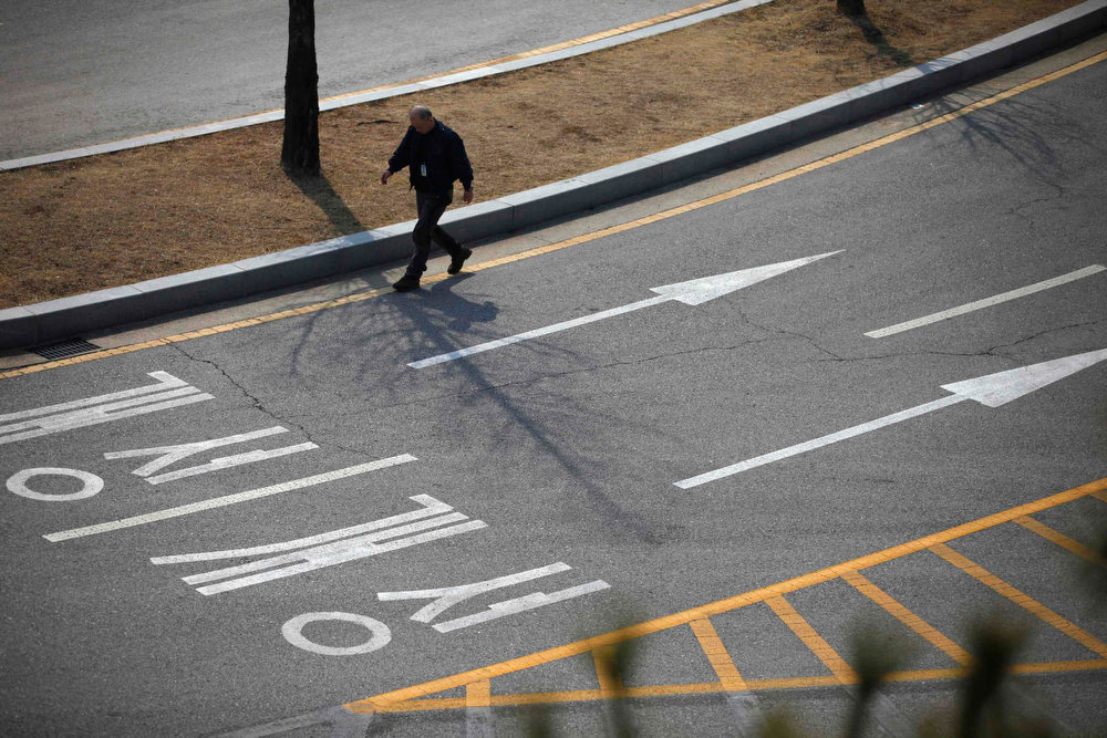 ". A South Korean worker walks on an empty road connecting the Kaesong Industrial Complex (KIC) with South Korea\'s CIQ (Customs, Immigration and Quarantine), just south of the demilitarized zone separating the two Koreas, in Paju, north of Seoul, April 3, 2013. North Korean authorities were not allowing any South Korean workers into a joint industrial park on Wednesday, South Korea\'s Unification Ministry and a Reuters witness said, adding to tensions between the two countries. The Korean characters on the road read as ""Kaesong\"". REUTERS/Kim Hong-Ji"