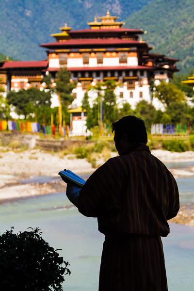 The Punakha Dzong is seen across the Mo Chhu River in central Bhutan while Buddhist prayer flags flutter nearby