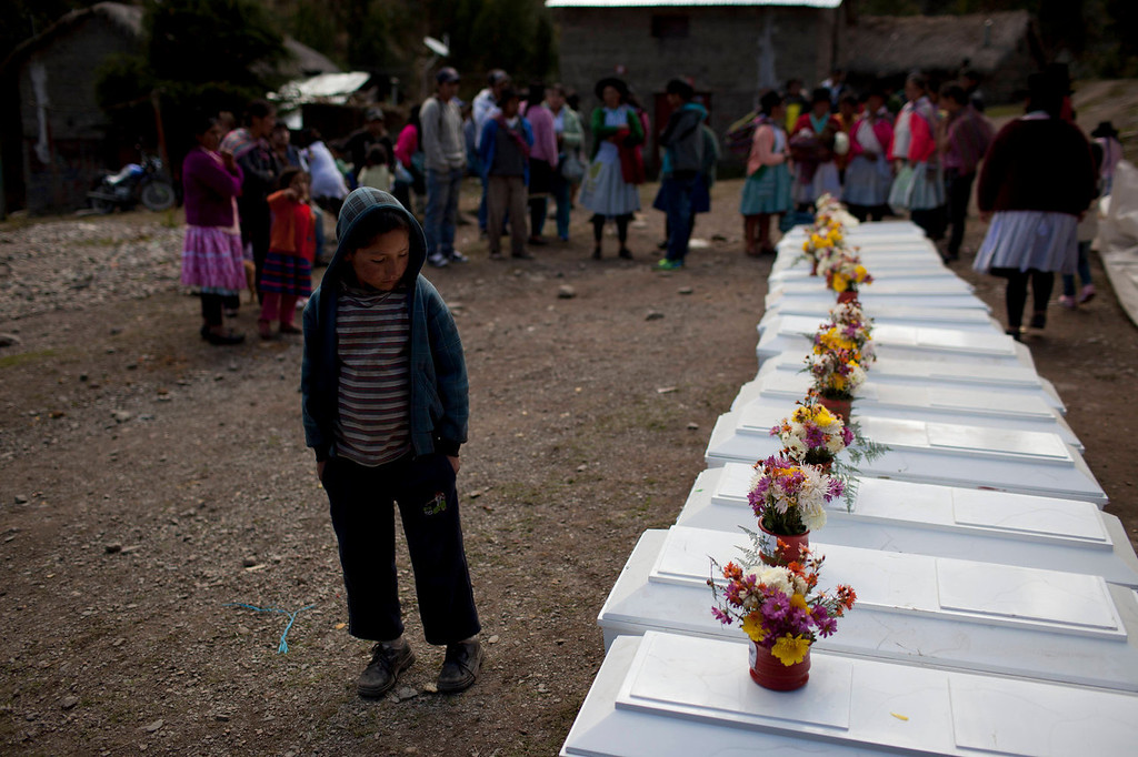 . A boy attending a mass funeral looks at a row of coffins containing the remains of villagers that were killed in a 1988 massacre, in Chaca, Peru. The boy joined other relatives of those slain by the Shining Path rebels nearly three decades ago, to formally bury the remains of the victims. The region endured some of the worst atrocities of Peru\'s 1980-2000 conflict, in which both Maoist-inspired insurgents and security forces committed grave human rights violations.   (AP Photo/Rodrigo Abd)
