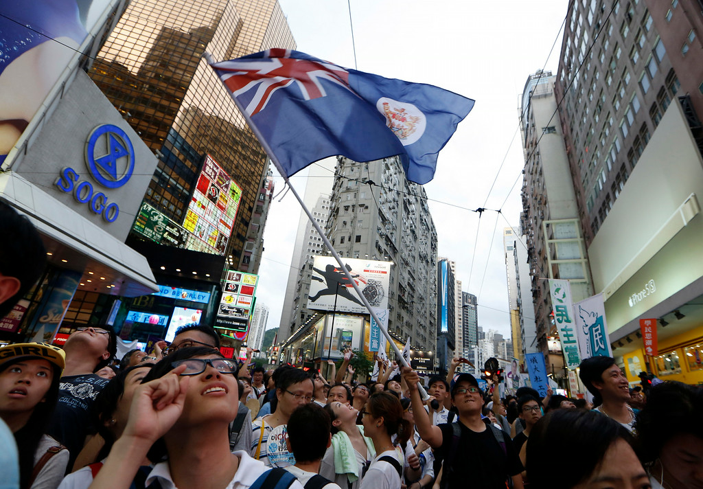 . A protester waves a Hong Kong colonial flag as people march during an annual protest in downtown Hong Kong Tuesday, July 1, 2014. Hong Kong residents marched through the streets of the former British colony to push for greater democracy in a rally fueled by anger over Beijing\'s recent warning that it holds the ultimate authority over the southern Chinese financial center. The protest comes days after nearly 800,000 residents voted in a mock referendum aimed at bolstering support for full democracy. (AP Photo/Kin Cheung)