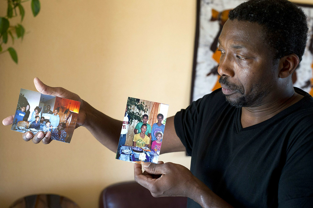 . Amadou Ouedraogo poses with pictures of his brother, Seydou and his family who were aboard the Air Algerie plane that crashed over Mali, on July 25, 2014 in Remouille, near Nantes, western France. France announced on July 25 there were no survivors among the passengers and crew, saying bad weather was the likely cause of the disaster. The wreckage of the McDonnell Douglas 83 plane, operated by Spanish charter firm Swiftair on behalf of Air Algerie, was located 50 kilometers (31 miles) north of the Burkina Faso border in Mali\'s Gossi region. AFP PHOTO / JEAN-SEBASTIEN EVRARD/AFP/Getty Images