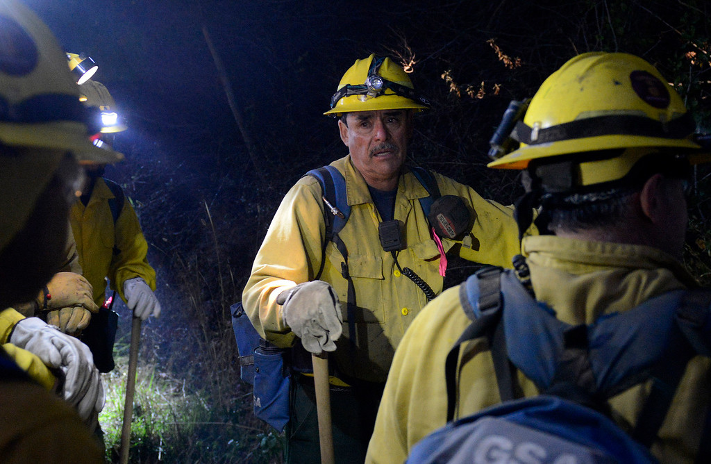 . Rudy Gutierrez and other members of a Sequoia National Forest fire crew head up off Highway 1 as dusk falls to battle the fire near the Big Sur Station from the Pfeiffer Ridge area in Big Sur, Calif. on Tuesday December 17, 2013. (Photo David Royal/ Monterey County Herald)