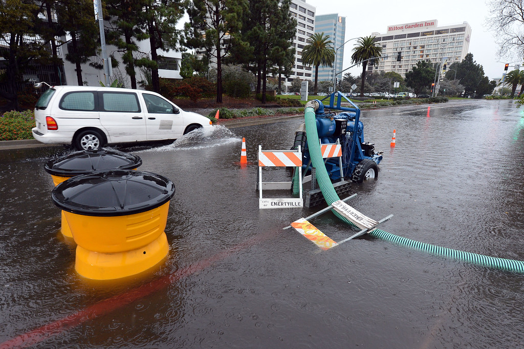 . Water is pumped from the street as a car plows through a flooded section of Powell Street in Emeryville, Calif., on Thursday, Dec. 11, 2014. (Kristopher Skinner/Bay Area News Group)