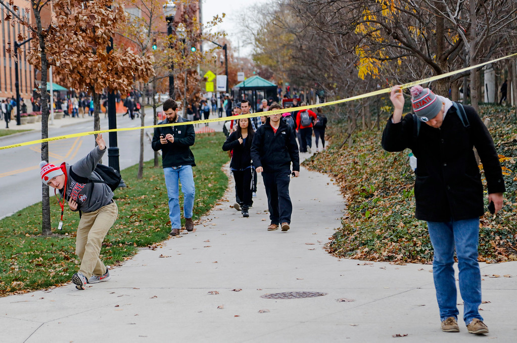 . Ohio State students duck under police tape after a shelter-in-place notification was lifted following an attack Monday, Nov. 28, 2016, at Ohio State University in Columbus, Ohio. (Joshua A. Bickel/The Columbus Dispatch via AP)