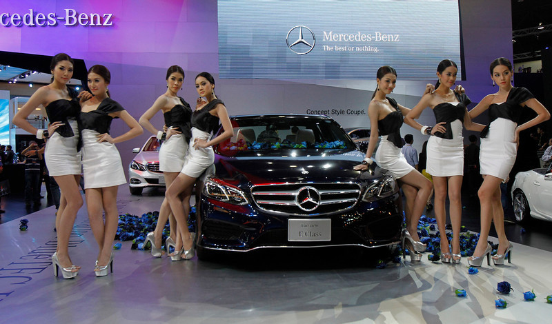 . Models pose beside the new Mercedes-Benz E Class during a media presentation of the 34th Bangkok International Motor Show in Bangkok March 26, 2013. The Bangkok International Motor Show will be held from March 27 to April 7. REUTERS/Chaiwat Subprasom