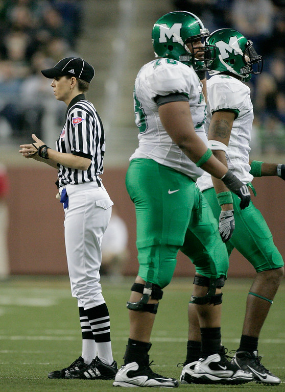 . Line judge Sarah Thomas, left, works the Little Caesars Pizza Bowl NCAA college football game as Marshall\'s Brandon Campbell, center, and Aaron Dobson, right, walk off the field Saturday, Dec. 26, 2009, in Detroit. Thomas is one of five women officiating in major college football, but Pizza Bowl spokesman Tim Moore said she was the first to draw an assignment for a Bowl Subdivision postseason game. (AP Photo/Duane Burleson)