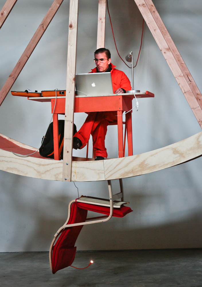 """. Alex Schweder use his laptop from a desk during the performance art \""""In Orbit,\"""" a 25-foot wheel made from wood, steel, and furniture, his home for 10 days along with fellow artist Ward Shelley at the Boiler gallery in the Brooklyn borough of New York, Tuesday, March 4, 2014. They will share two living units arrayed over the hamster-wheel-like sculpture, with Shelly living on the outside and Schweder on the inside. The structure will remain on view through April 5.  (AP Photo/Bebeto Matthews)"""