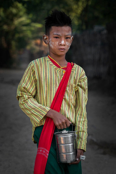 A young boy heads to school with his warm home made food in a flask.  Myanmar 2017