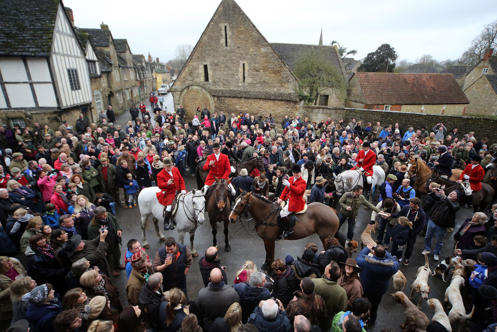 Description of . Stuart Radbourne, (centre foreground) huntsman and joint-master with the Avon Vale Hunt, toasts supporters who have gathered for their traditional Boxing Day hunt, on December 26, 2012 in Lacock, England. As hundreds of hunts met today, Environment Secretary Owen Paterson claimed that moves to repeal the ban on hunting with dogs in England and Wales may not happen in 2013, although he insisted it was still the government's intention to give MPs a free vote on lifting the ban.  (Photo by Matt Cardy/Getty Images)