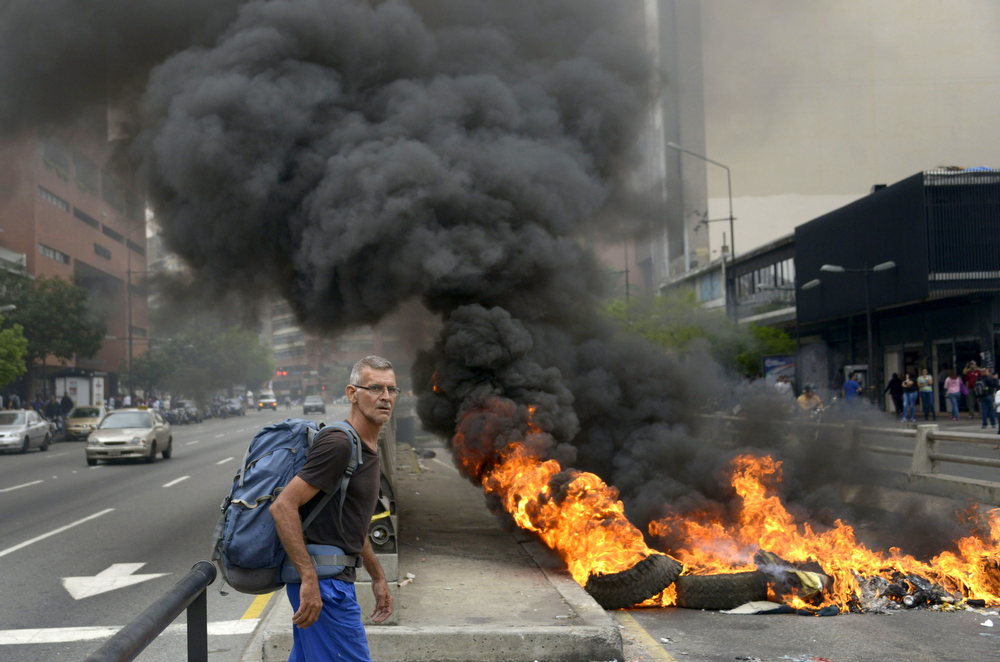 . A man passes by a barricade set ablaze blocking a street during a protest against the government of Venezuelan President Nicolas Maduro, in Caracas on February 24, 2014. At least 25 people were injured in late Saturday clashes with security forces that were some of the most serious to date. Venezuela\'s president on Sunday called for crisis talks in an attempt to defuse weeks of often deadly anti-government protests that have brought the biggest challenge yet to his regime. (RAUL ARBOLEDA/AFP/Getty Images)