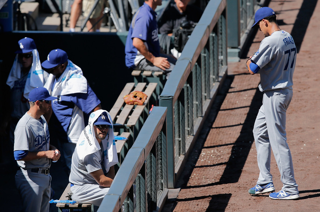 . DENVER, CO - SEPTEMBER 17:  Starting pitcher Carlos Frias #77 of the Los Angeles Dodgers walks to the dugout after being removed from the game against the Colorado Rockies in the first inning at Coors Field on September 17, 2014 in Denver, Colorado. Frias allowed eight runs by the Rockies before being removed in the first inning.  (Photo by Doug Pensinger/Getty Images)