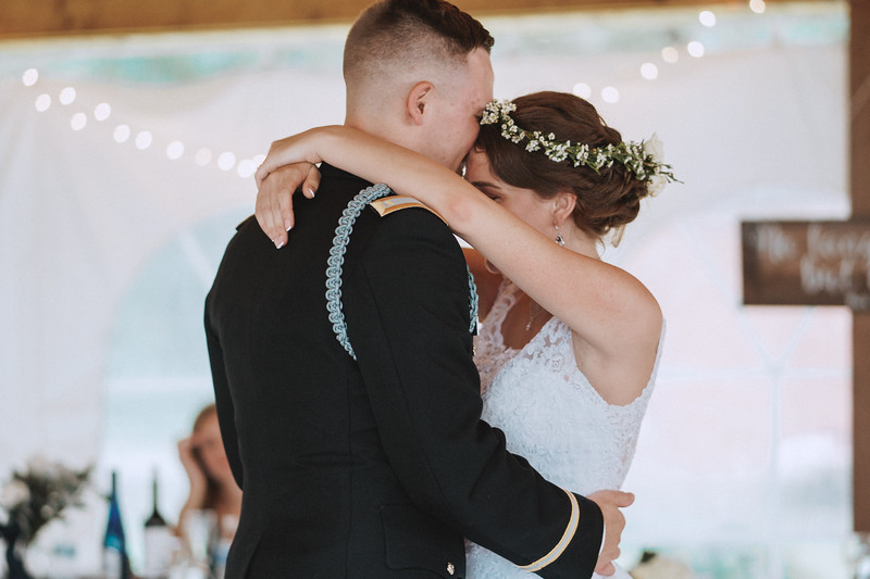 The groom kisses the brides forehead as they dance.