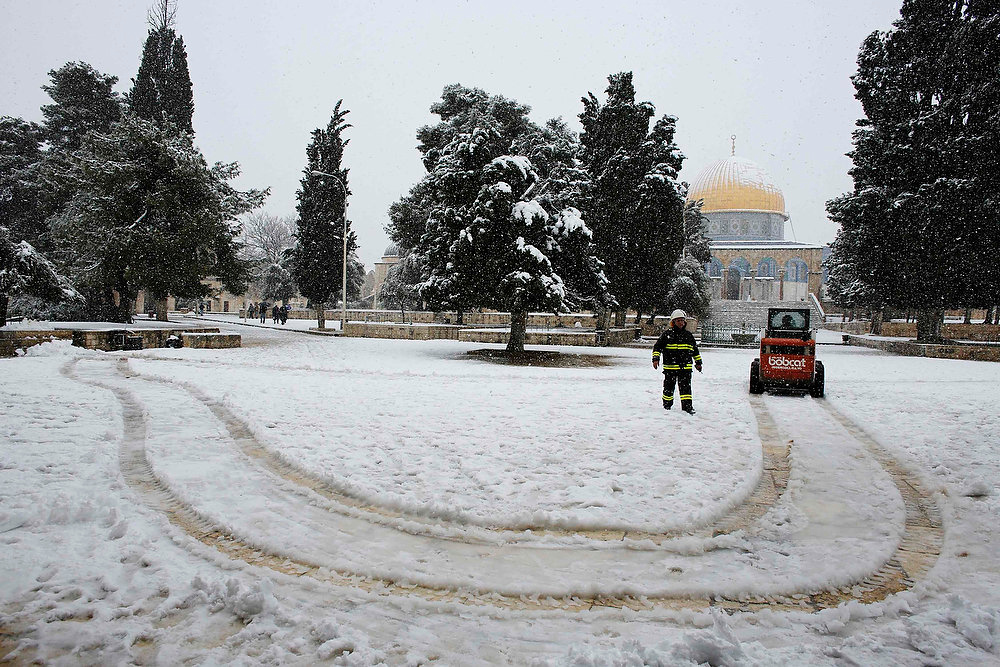 Description of . A Palestinian worker stands next to a snowplow in front of the Dome of the Rock on the compound known to Muslims as al-Haram al-Sharif and to Jews as Temple Mount, in Jerusalem's Old City during a snowstorm January 10, 2013. The worst snowstorm in 20 years shut government offices, public transport and schools in Jerusalem and along the northern Israeli region bordering on Lebanon on Thursday. REUTERS/Ammar Awad