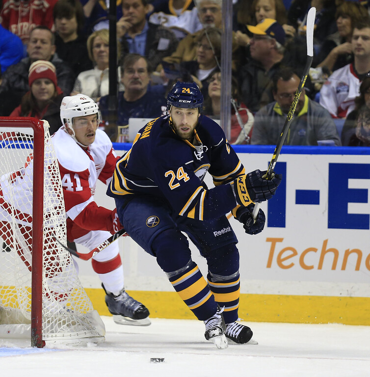 . Buffalo Sabres Tyson Strachan (24) tries to move the puck past Detroit Red Wings Luke Gledening (41) during first period action of an NHL hockey game, Sunday, Nov. 2, 2014, in Buffalo, N.Y. (AP Photo/The Buffalo News, Harry Scull Jr)