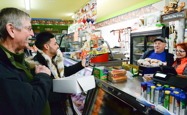 02/28/19 Wesley Bunnell | Staff Former New Britain Mayor Lucian Pawlek, L, looks on as New Britain Flower Shop owner Nick Erlacher takes a photo of the owners of Zieleniak Deli Slawek and Beata Rulka stand with a tray of freshly made paczki.